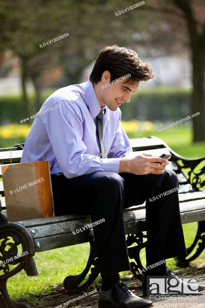 Stock Photo: A businessman sitting on a bench, using his mobile phone.