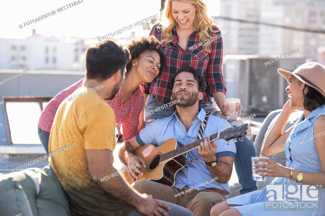 Imagen: Friends having a rooftop party and playing guitar.