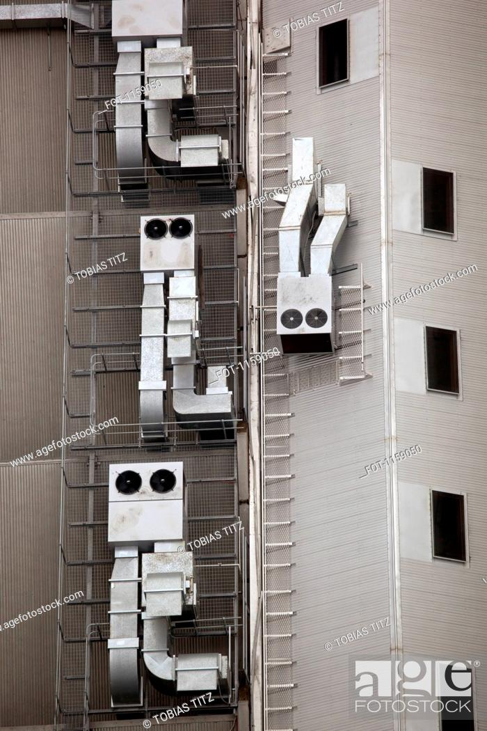 Stock Photo: Anthropomorphic air vents on side of building.