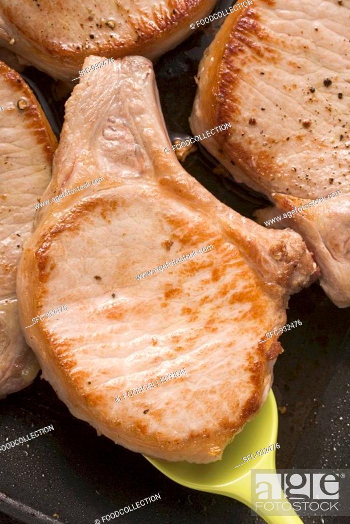 Stock Photo: Fried pork chops in frying pan.