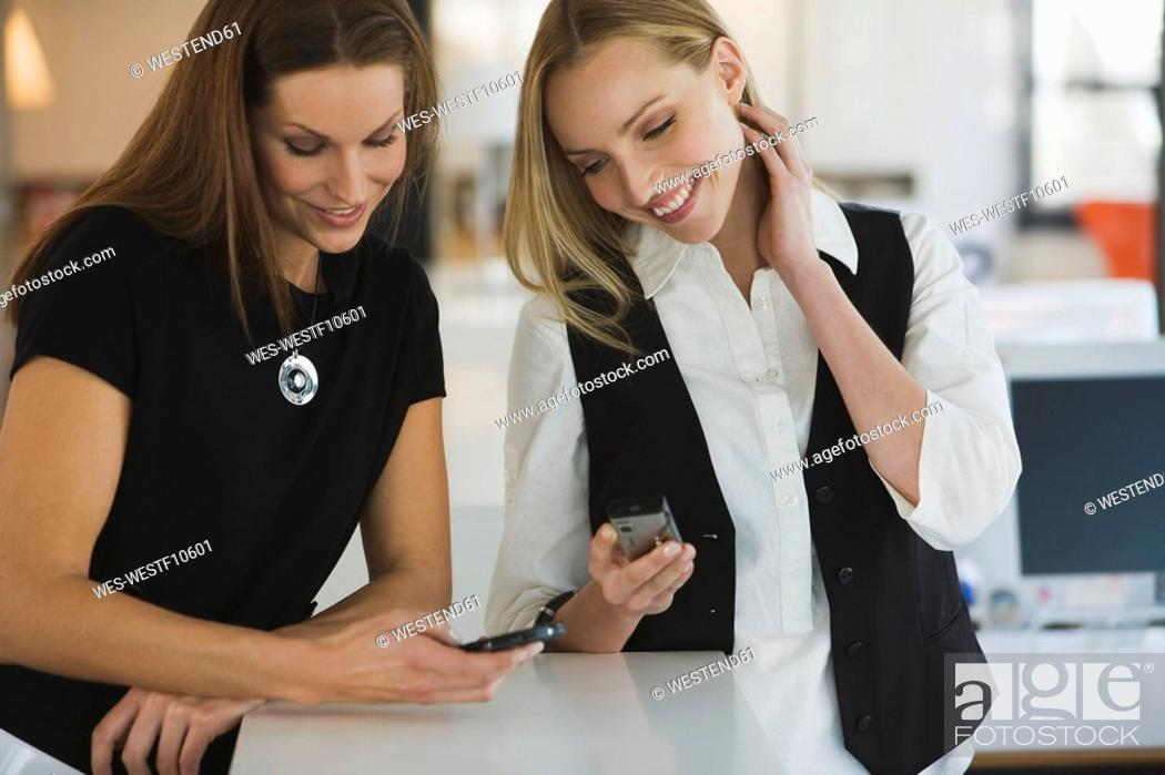 Stock Photo: Two women in office using mobile phones, smiling.