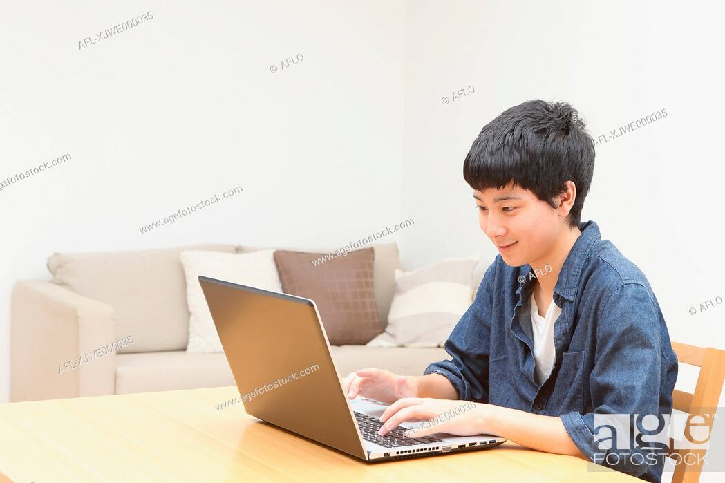 Stock Photo: Young Japanese man working with notebook.