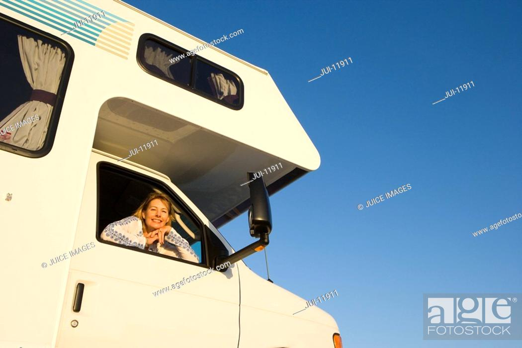 Stock Photo: Mature woman looking out window of motor home, smiling, portrait, low angle view.