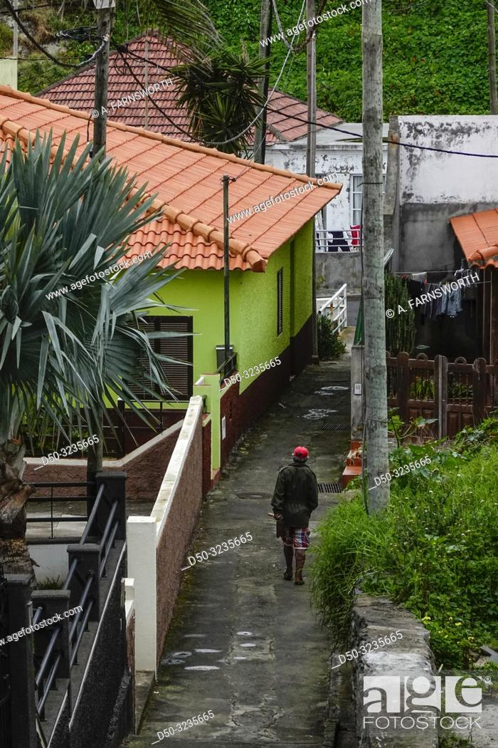 Imagen: Madeira, Portugal A man walks in a tropical back alley of Canical.