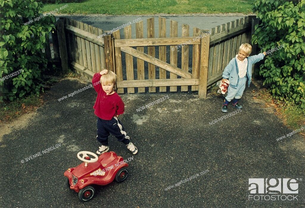 Stock Photo: Two boys playing in front of a gate.