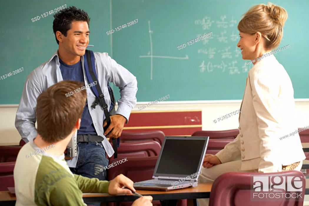 Stock Photo: Side profile of a professor and two college students smiling in a lecture hall.