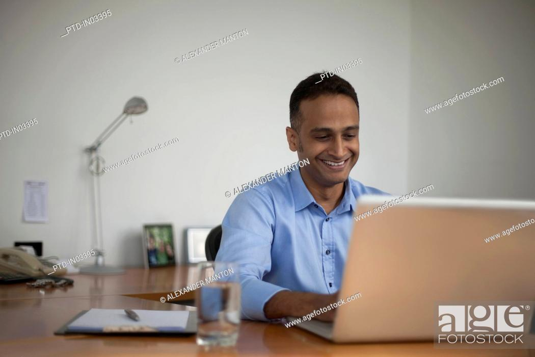 Stock Photo: Singapore, Smiling businessman working at laptop in office.