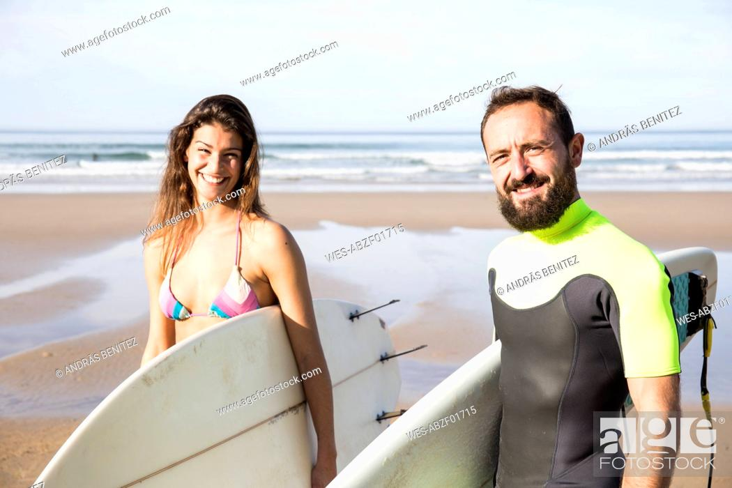 Stock Photo: Happy couple carrying surfboards on the beach.