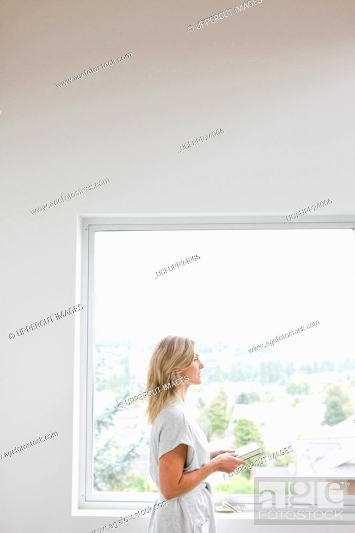 Stock Photo: Woman walking past window with book.