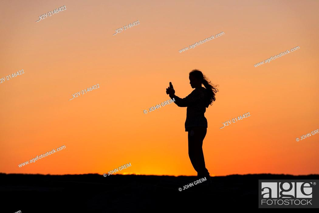 Stock Photo: Girl with mobile phone enjoys the sunset from a jetty.