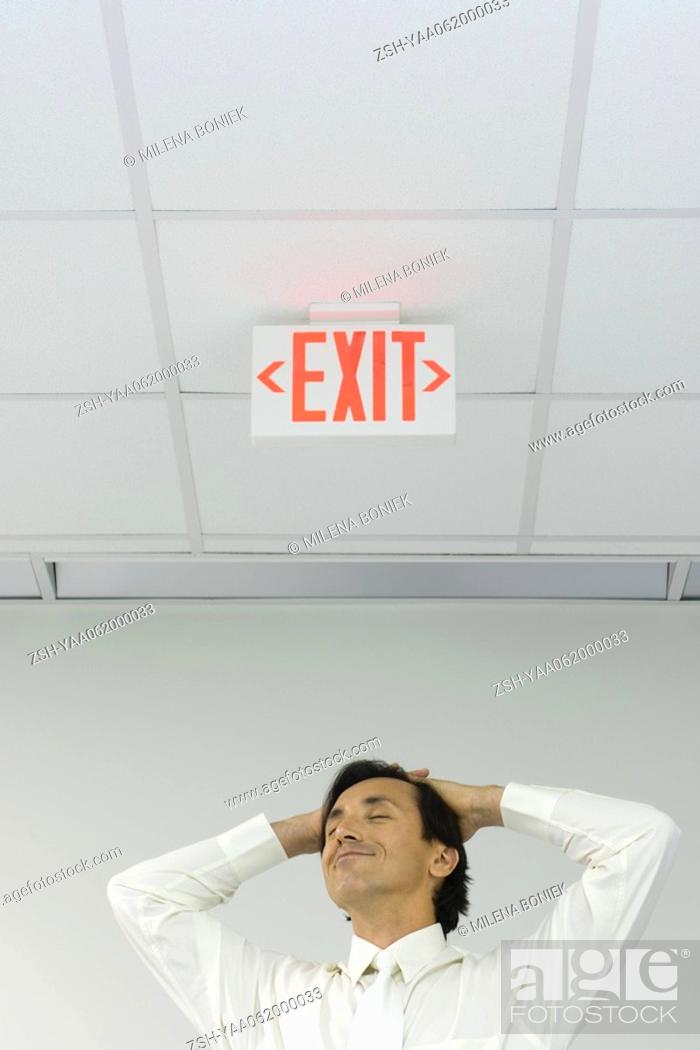 Stock Photo: Man beneath exit sign with eyes closed, hands on head, smiling, low angle view.