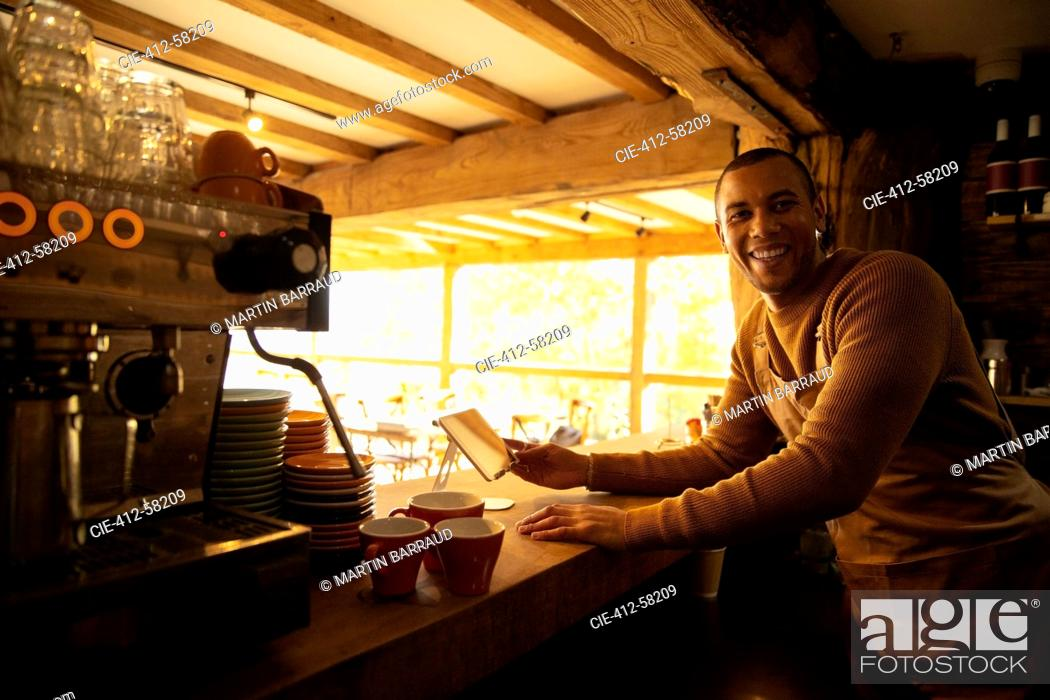 Stock Photo: Portrait happy male coffee shop owner working behind counter.