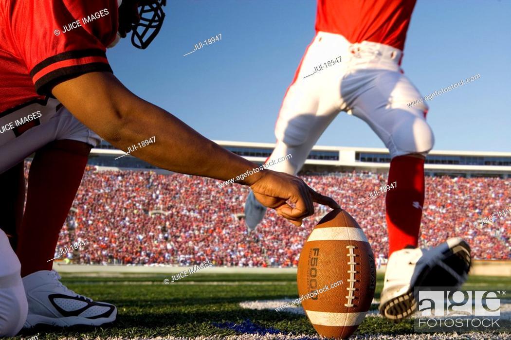 Stock Photo: Kicker kicking football.