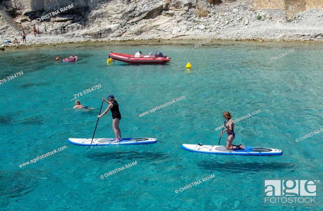 Stock Photo: MALLORCA, SPAIN - JUNE 23, 2019: Stand up paddlers on clear turquoise water near the shore on a sunny day on June 23, 2019 in Mallorca, Spain.