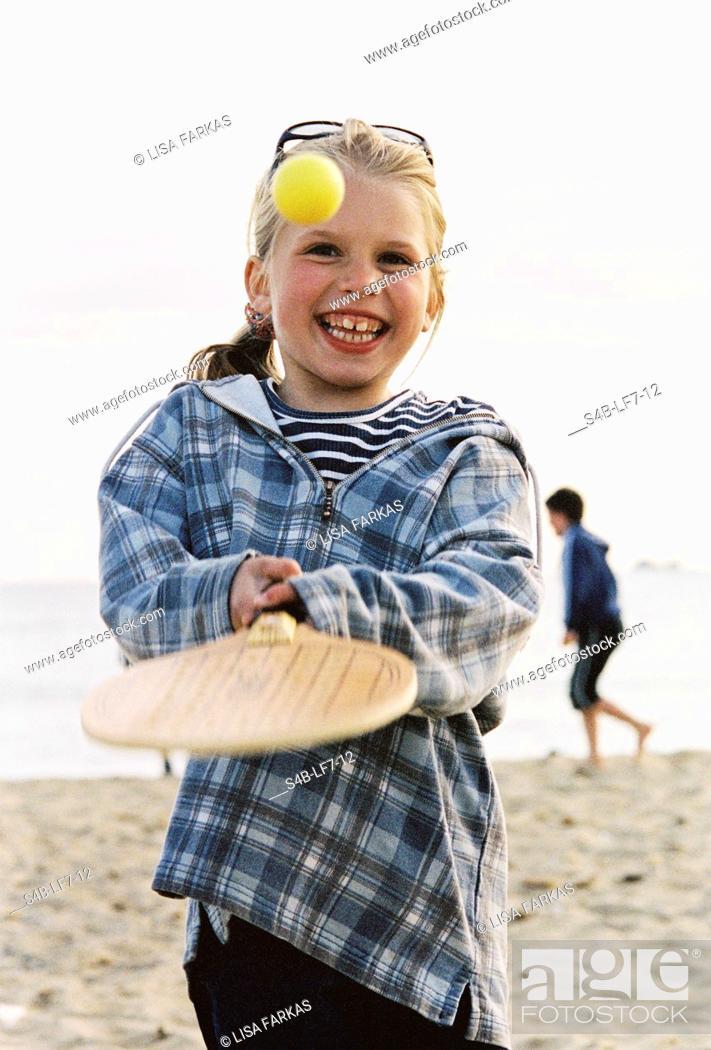 Stock Photo: Girl 6-7 years playing with checkerbat racket at beach, Elba island, Tuscany, Italy.