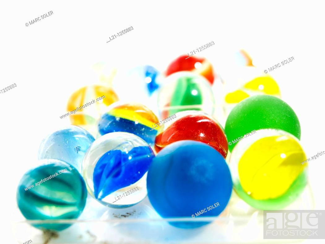 Stock Photo: Glass marbles in a plastic box, white background.