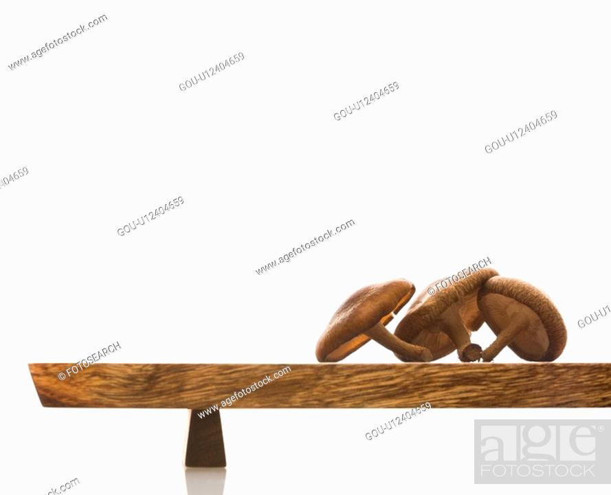 Stock Photo: Three brown mushrooms on wooden cutting board with white background.