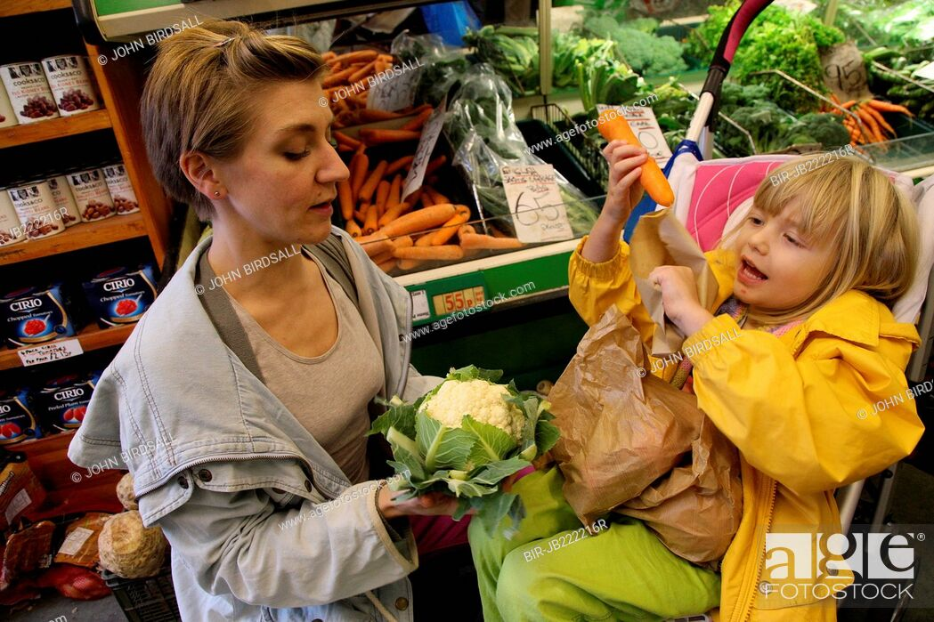 Stock Photo: Mother with toddler in buggy shopping for vegetables.