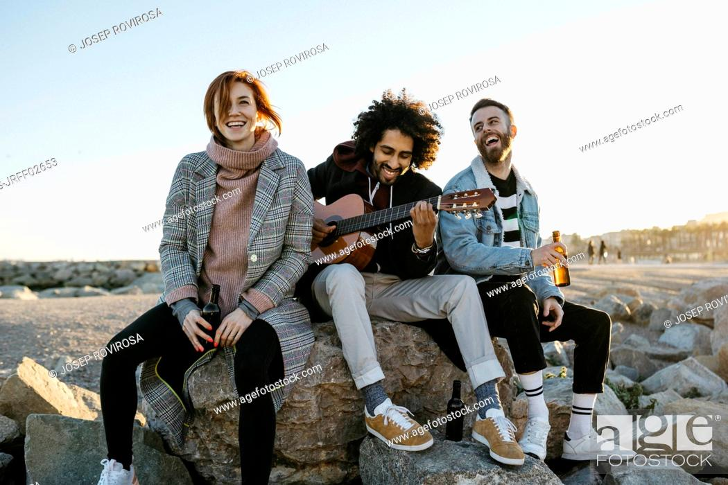 Imagen: Three happy friends with guitar sitting outdoors at sunset.
