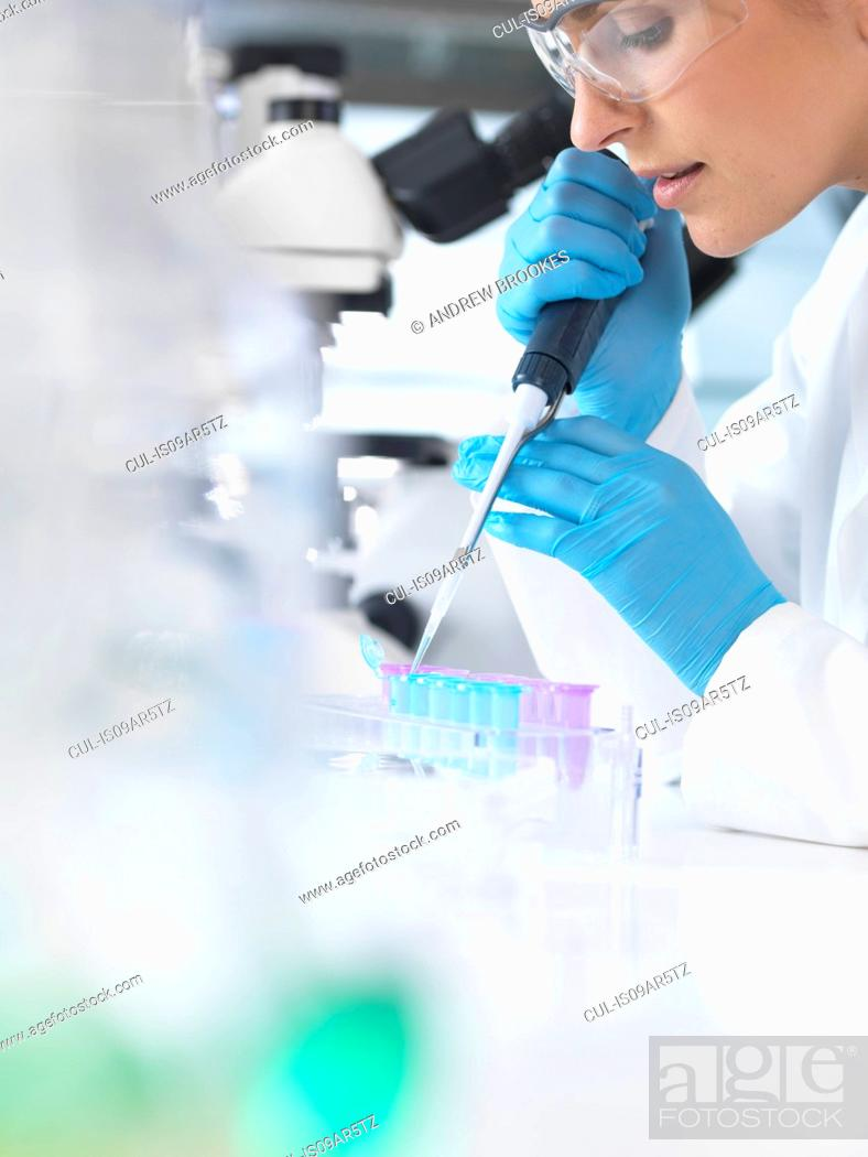Imagen: Female scientist pipetting sample into a vial for analytical testing in a laboratory.