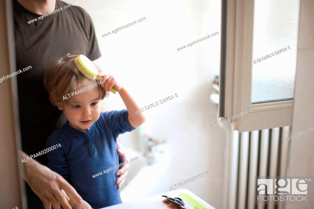 Stock Photo: Young boy learning to brush his hair.