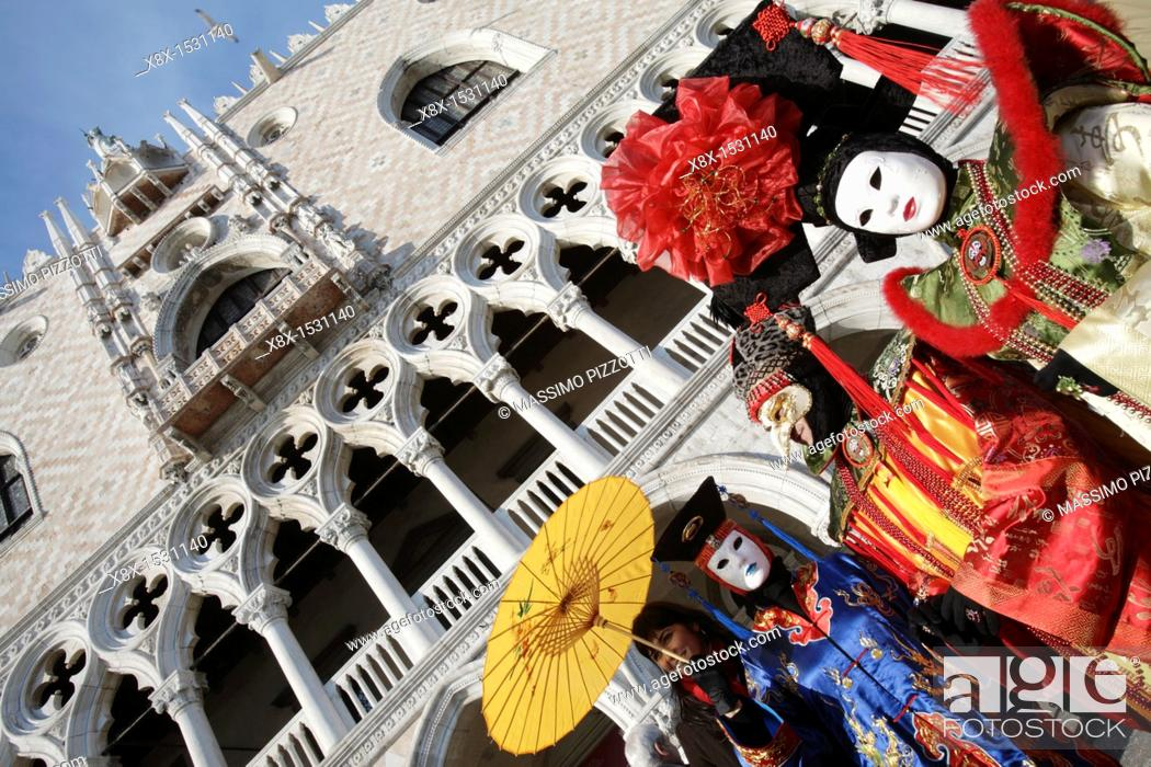 Stock Photo: Chinese venetian mask at the Venice Carnival 2007, with the Doge's palace in the background, Venice, Italy.