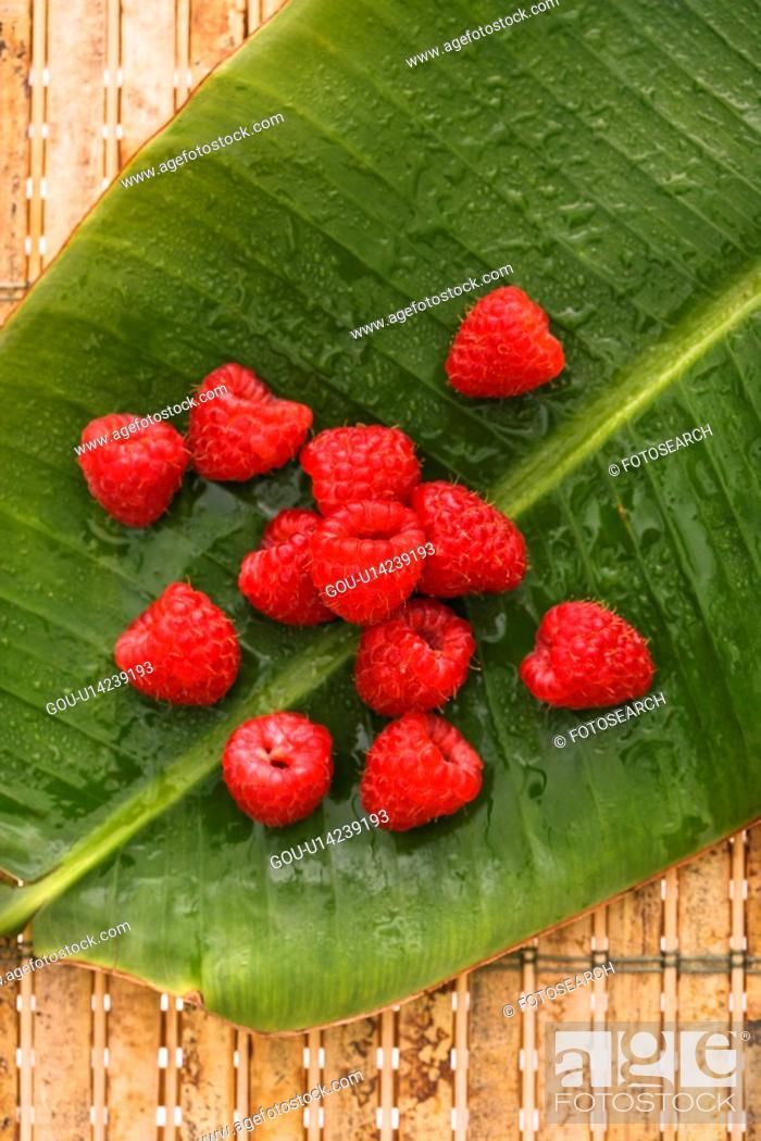 Stock Photo: Still life of red raspberries on banana leaf.