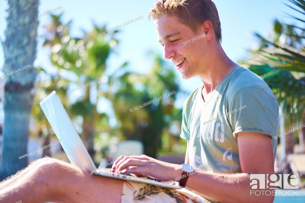 Imagen: young man with laptop computer sitting outside.