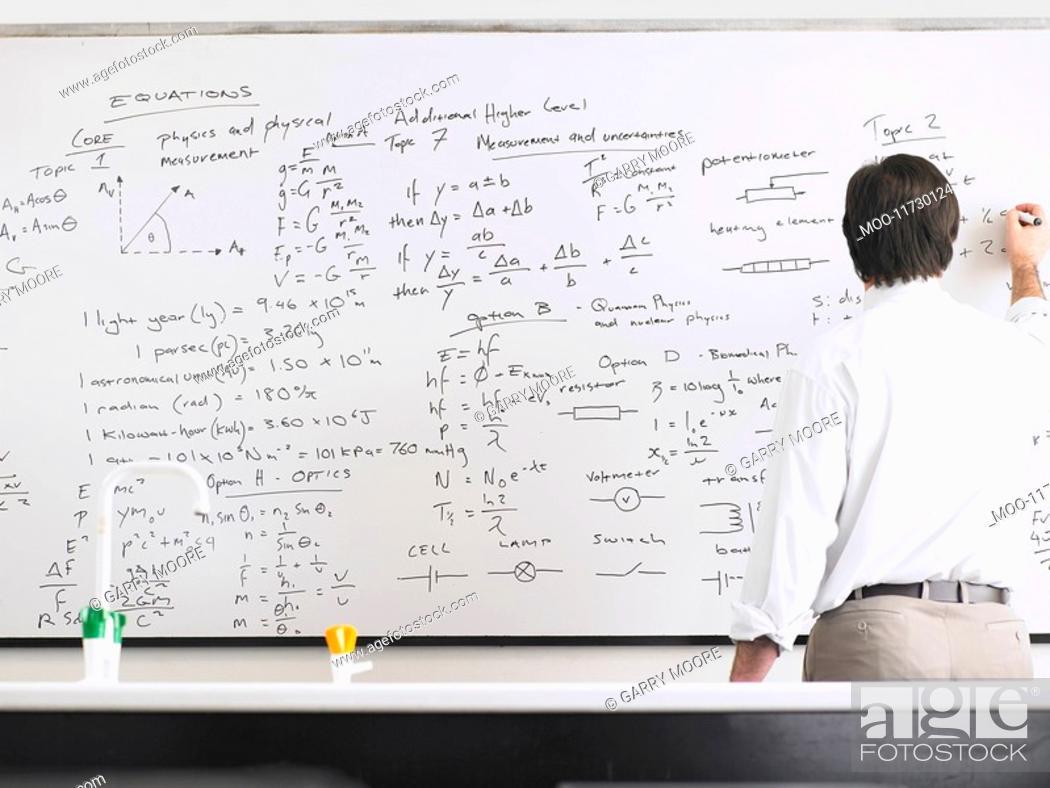 Stock Photo: Teacher writing on whiteboard back view.