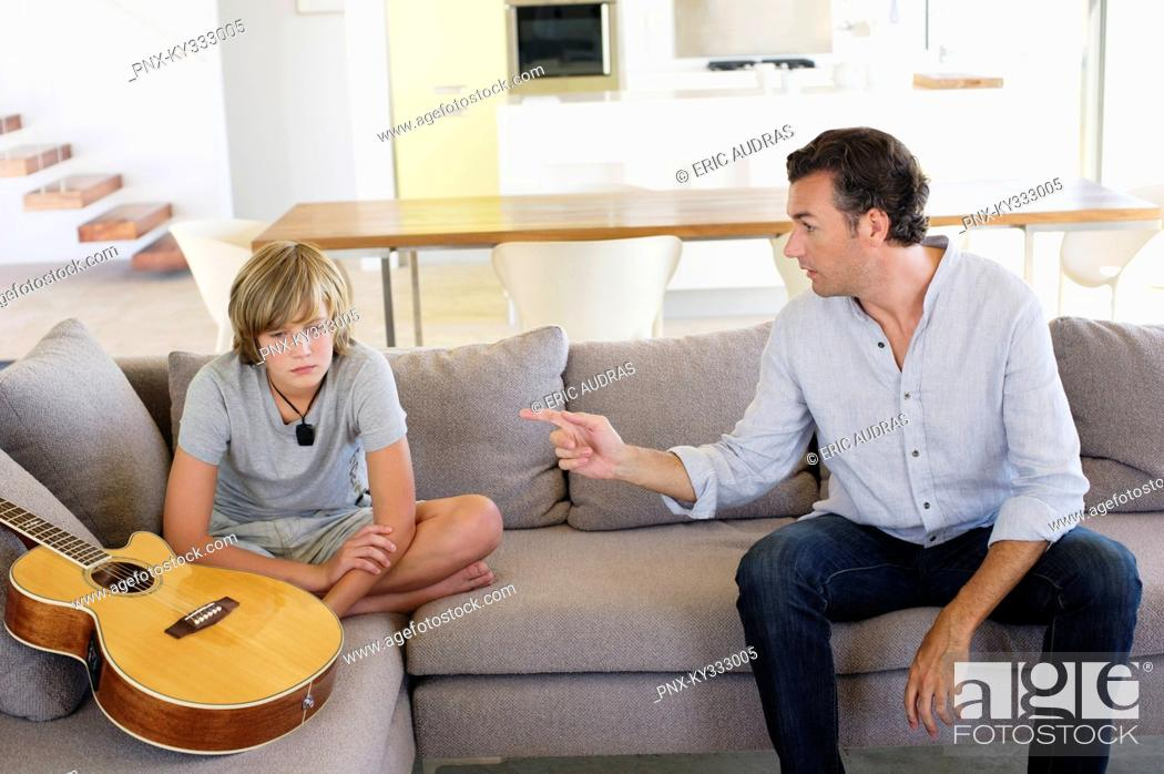 Stock Photo: Father complaining to teenage boy sitting with guitar at home.