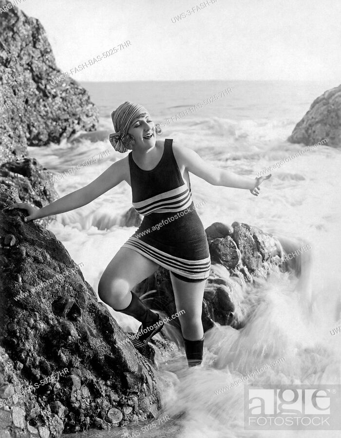 Stock Photo: Los Angeles, California: c. 1922.A flapper in a bathing suit, scarf, and footwear plays in the surf on a rock at the beach.
