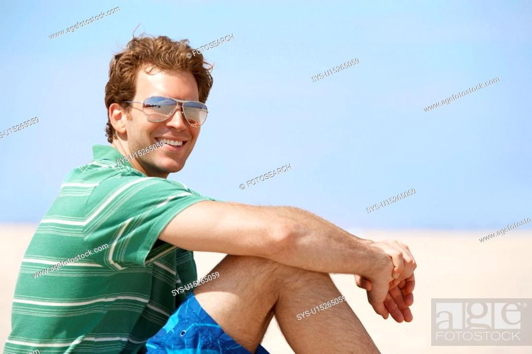 Stock Photo: Young man smiling at beach.