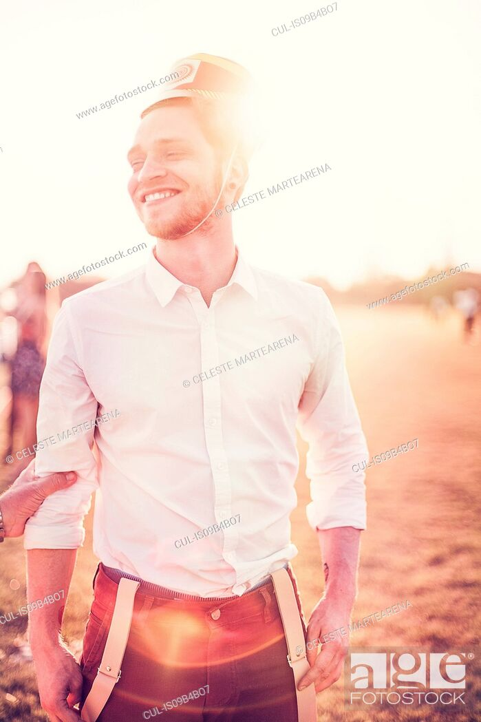 Stock Photo: Young man in party hat laughing in sunlit field, Tucuman, Argentina.