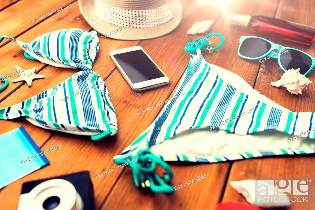 Stock Photo: vacation, travel, tourism, technology and objects concept - close up of smartphone and beach stuff.