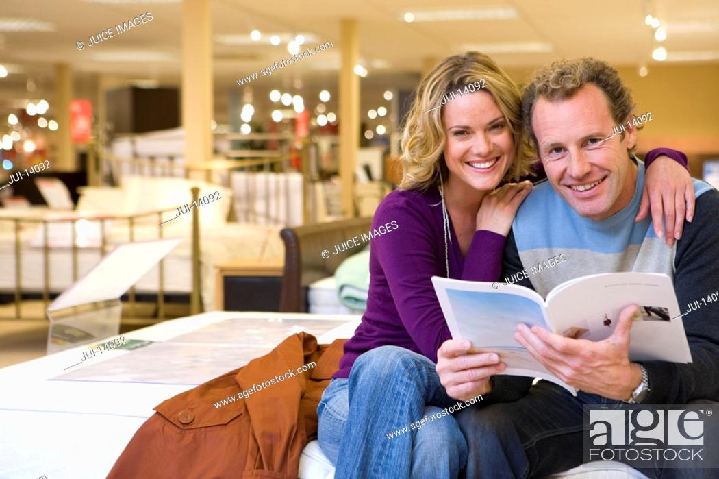 Stock Photo: Young couple in furniture shop, woman embracing man with brochure, smiling, portrait.