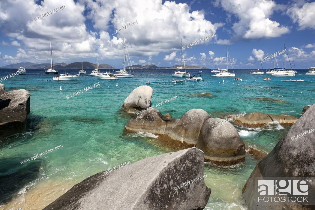 Stock Photo: Boulders dot the shoreline of the Baths with boats moored in the distance at the Baths on Virgin Gorda in the British Virgin Islands.