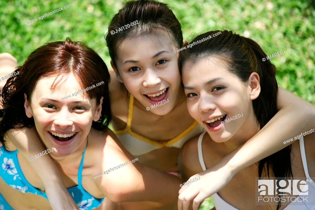 Stock Photo: Portrait of three teenage girls with arms around each other.