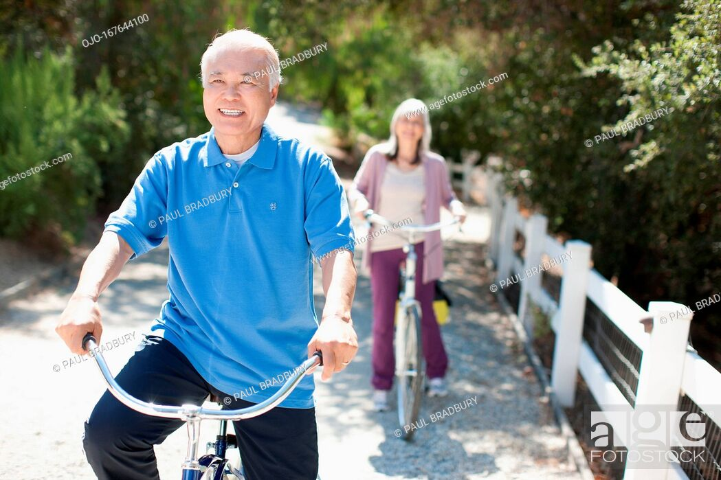 Stock Photo: Smiling older couple riding bicycles.