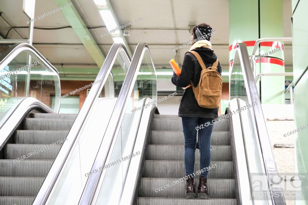 Stock Photo: University female african student wearing protective face mask taking escalator upstairs at the underground station. New normal in public transport.