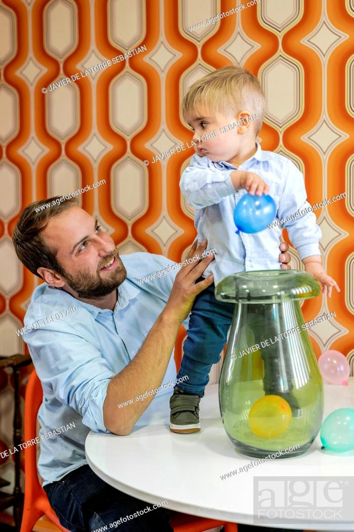 Stock Photo: Smiling father looking at son playing with balloons on table.