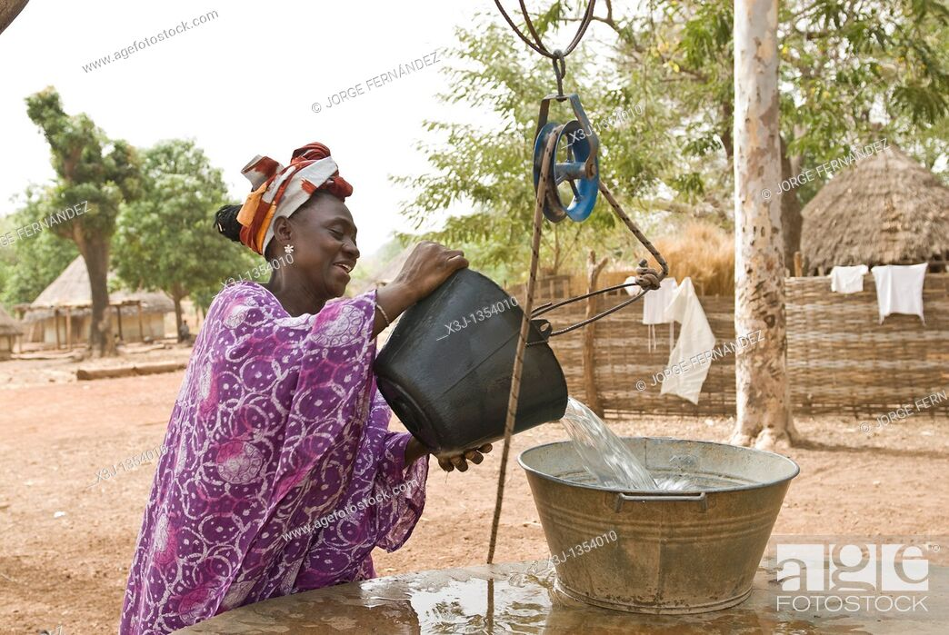 Stock Photo: African Bassari women with headscarf hauling water from a well , Salemata village, Bassari country, Senegal, Africa.