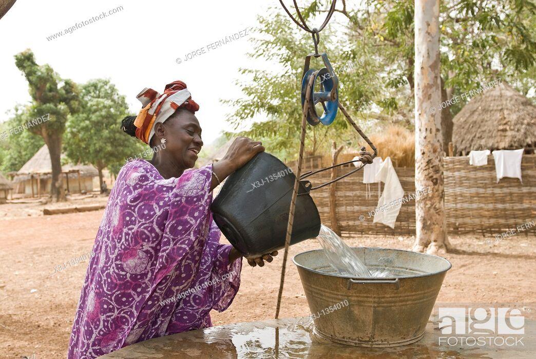 Imagen: African Bassari women with headscarf hauling water from a well , Salemata village, Bassari country, Senegal, Africa.