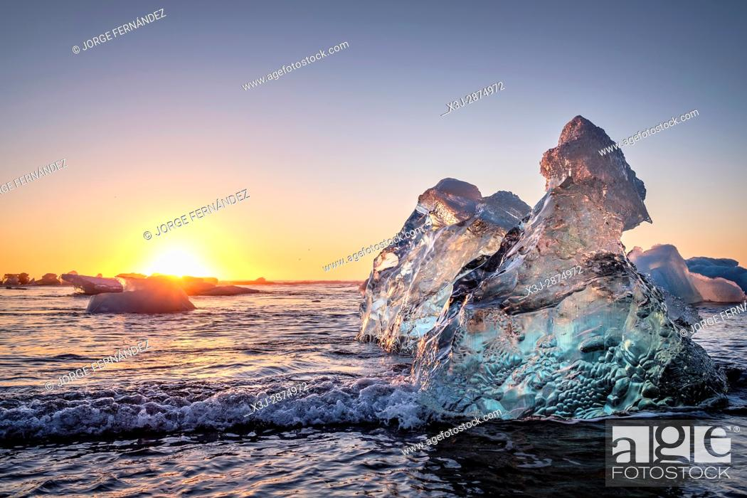 Stock Photo: Sunrise of a very clear day over the pieces of ice shed from the Jokullsarlon glaciers pushed to the seashore at the Jokulsarlon Ice Beach.