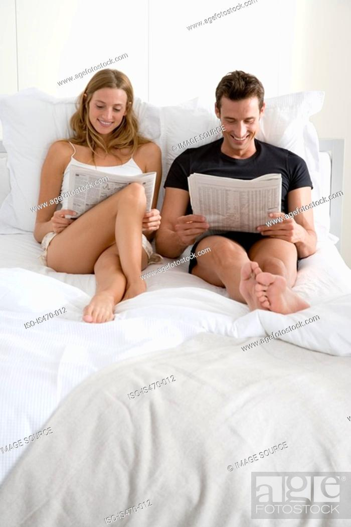 Stock Photo: Couple reading newspapers on bed.