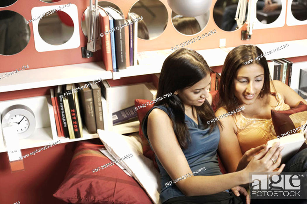 Stock Photo: High angle view of two young women reading a book.