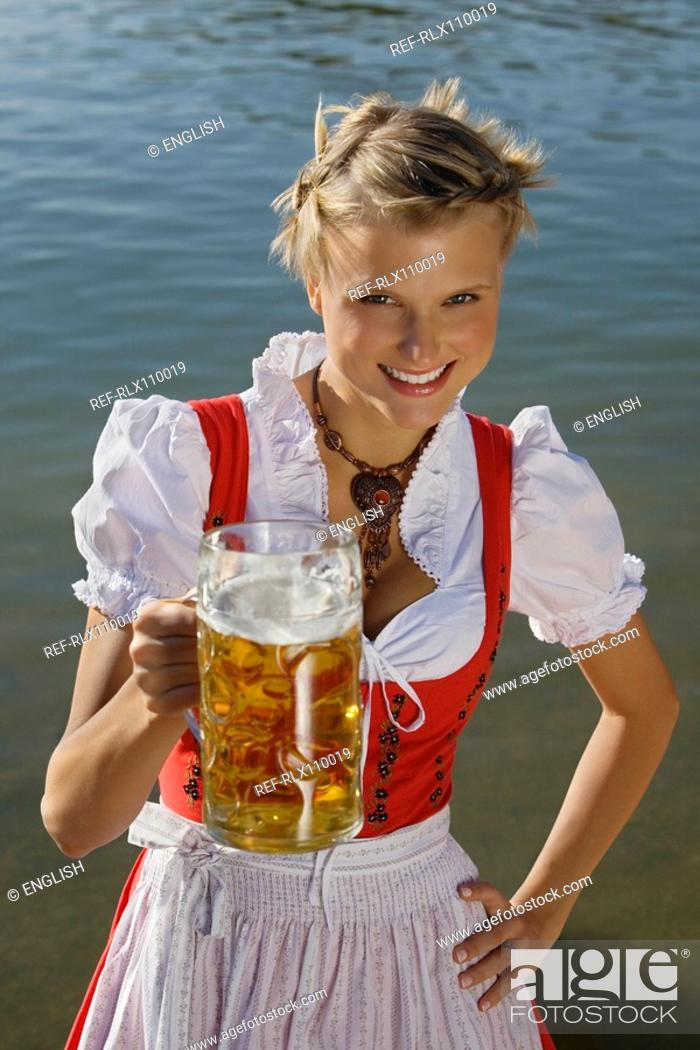 Stock Photo: Young woman in traditional Bavarian dress, holding litre glass of beer.