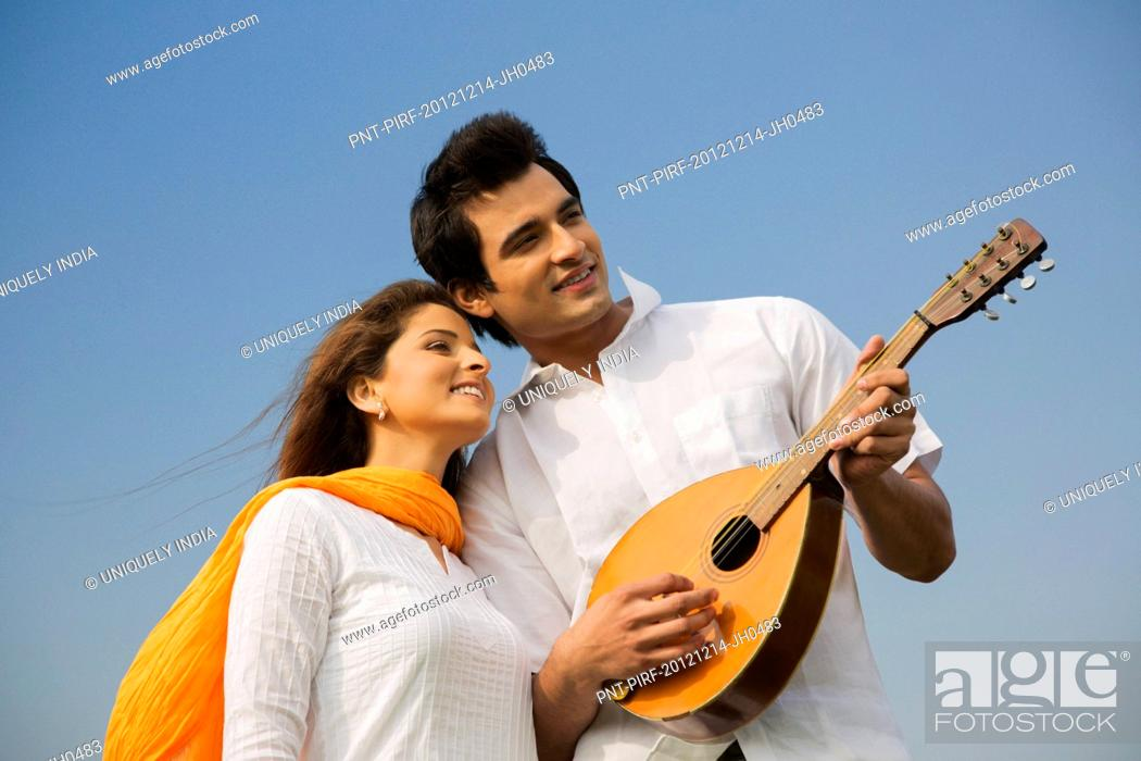 Imagen: Couple playing a mandolin and smiling.