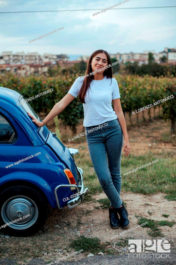 Stock Photo: Portrait of woman leaning against car in countryside, Florence, Toscana, Italy.