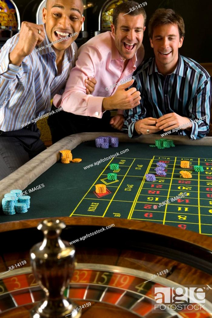 Stock Photo: Young man and friends gambling at roulette table in casino, smiling.