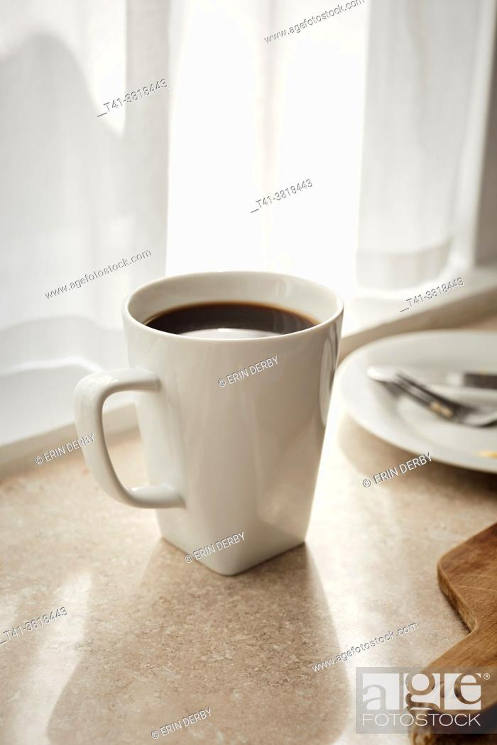 Stock Photo: A white mug of coffee sitting on a counter of a sun streaked kitchen.